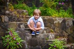 Enfant s'asseyant sur des étapes Images libres de droits