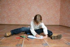 Enfant s'asseyant sur l'étage et le dessin Photos libres de droits