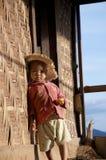 Enfant s'asseyant sur l'étape dans le village Images stock