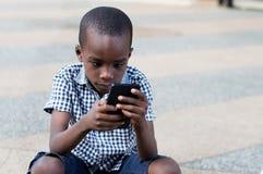 Enfant s'asseyant sur la terrasse avec un téléphone portable Photo stock