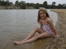 Enfant s'asseyant sur un banc de sable. Image stock