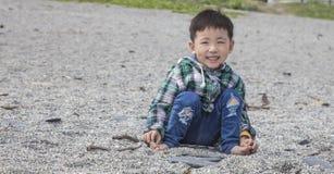 Enfant s'asseyant sur une plage Image stock