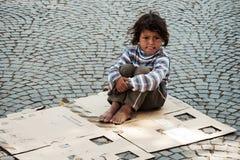 Enfant sans abri inconnu s'asseyant sur la rue Photographie stock