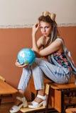 Enfant sauvage dans la classe de géographie avec le globe Photographie stock libre de droits