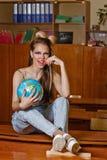 Enfant sauvage dans la classe de géographie avec le globe Image libre de droits