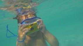 Enfant se baignant dans l'océan et prenant des photos avec l'appareil-photo imperméable banque de vidéos