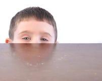 Enfant se cachant derrière la table de cuisine image stock