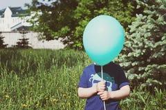 Enfant se cachant derrière le ballon Photographie stock libre de droits