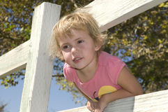 Enfant se penchant au-dessus d'une frontière de sécurité images stock