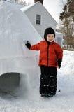 Enfant se penchant sur un igloo photos stock