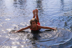 Enfant se situant dans l'eau ayant l'amusement et répandant des bras Image libre de droits