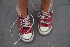 Enfant se tenant dans des chaussures de mamans Photo libre de droits