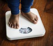 Enfant se tenant sur l'échelle de poids photographie stock libre de droits