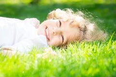 Enfant se trouvant sur l'herbe Image stock