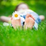 Enfant se trouvant sur l'herbe Photographie stock libre de droits
