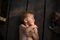 Enfant se trouvant sur les conseils avec ses amis Photos stock