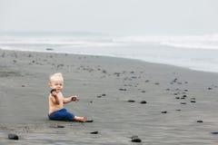 Enfant seul s'asseyant sur la plage noire de mer de sable Photos stock