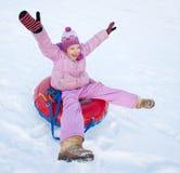 Enfant sledding en colline d'hiver Image libre de droits