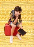 Enfant sombre se sentant fatigué tout en se reposant sur le bagage photographie stock