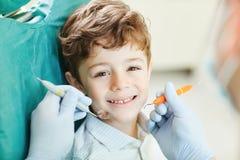 Enfant souriant tout en se reposant dans la chaise du dentiste images libres de droits