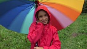Enfant sous la pluie, jeu d'enfant extérieur dans le parapluie de rotation de fille de parc sur pleuvoir le jour clips vidéos