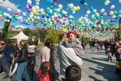 Enfant sur des mains du ` s de père ayant l'amusement avec la famille au festival Tbilisoba de ville Photographie stock