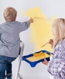 Enfant sur l'échelle peignant le mur Photo libre de droits