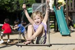 Enfant sur l'oscillation de cour de jeu Photographie stock
