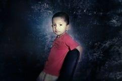 enfant sur la chaise regardant l'appareil-photo Photo stock