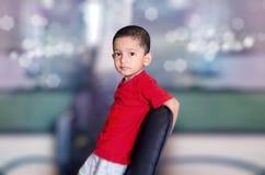enfant sur la chaise regardant l'appareil-photo Photo libre de droits