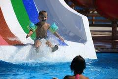 Enfant sur la glissière d'eau à l'aquapark Images libres de droits