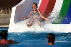 Enfant sur la glissière d'eau à l'aquapark Photo stock