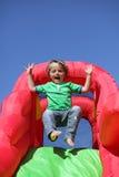 Enfant sur la glissière pleine d'entrain gonflable de château Photos stock