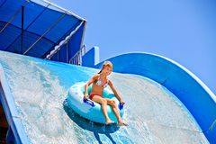 Enfant sur la glissière d'eau à l'aquapark Photo libre de droits