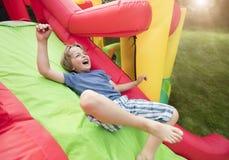 Enfant sur la glissière pleine d'entrain gonflable de château Photo stock