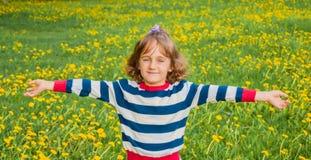 Enfant sur la pelouse avec des pissenlits Images stock