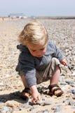 Enfant sur la plage avec des cailloux Image stock
