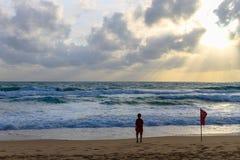 Enfant sur la plage regardant la mer et triste Images stock