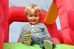 Enfant sur le château plein d'entrain gonflable Image libre de droits