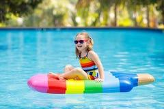 Enfant sur le flotteur gonflable dans la piscine photo libre de droits