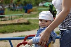 Enfant sur le rond point Photos stock