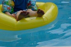 Enfant sur le tube dans la piscine Photos stock