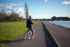 Enfant sur le vélo sur le chemin par la rivière images libres de droits