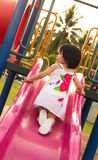 Enfant sur une glissière dans la cour de jeu Photos libres de droits