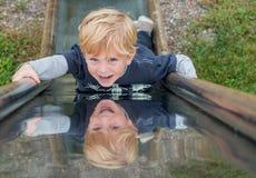 Enfant sur une glissière en métal Photo libre de droits