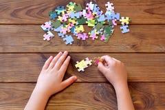 Enfant tenant des puzzles dans des mains Un ensemble de puzzles denteux sur la table en bois Photos libres de droits