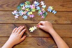Enfant tenant des puzzles multicolores dans des mains Premier concept d'éducation Photos stock
