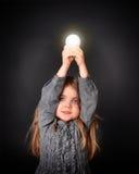 Enfant tenant l'ampoule lumineuse Image stock