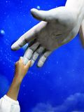 Enfant tenant la main de Jesus Statue Photo stock