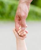 Enfant tenant la main du père Photos libres de droits